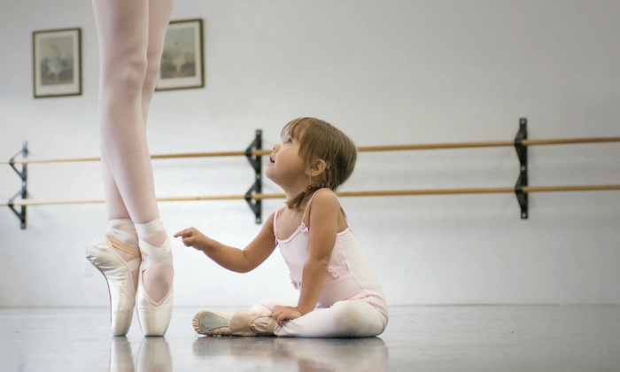 Baby sat next to a ballerina in en pointe pose